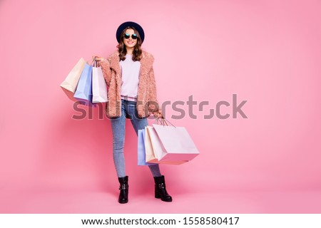 Photo of young joyful woman with shopping bags on the background stock photo © HASLOO