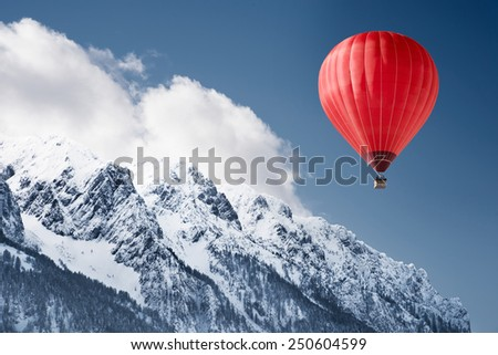 Stock photo: Mountain landscape with snow and hot air balloon flying in the s