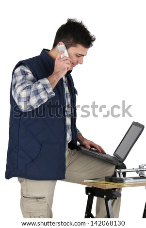 Stock photo: Tradesman posing with his building materials and embracing modern technology