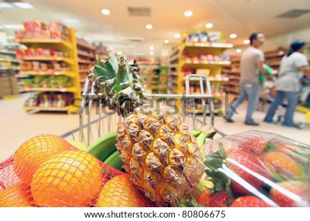 Stock photo: Moving shopping cart in supermarket. It was taken with a slow sh