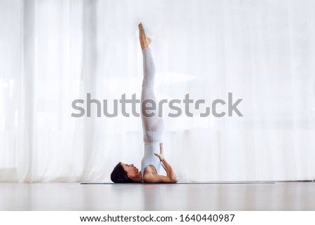 Side view of woman in the shoulder stand position on yoga mat  Stock photo © wavebreak_media