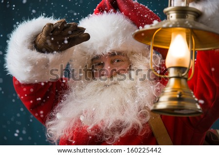 Stock photo: Santa Claus Is Holding A Shining Lantern While Sneaking To His H
