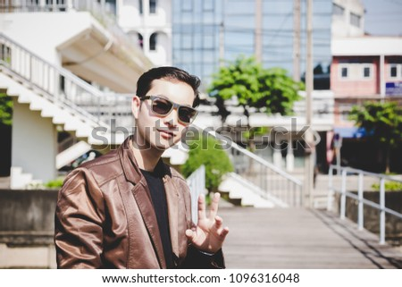 young business man wearing a leather jacket enjoying his cigaret stock photo © feedough
