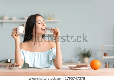 young beautiful caucasian woman eating a chocolate bar and looking at the camera stock photo © ambro
