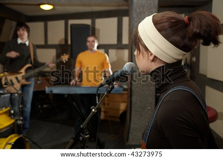 Vocalist girl near microphone. focus on head of microphone. electro guitar player and keyboarder in  stock photo © Paha_L