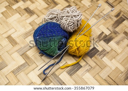 Stock photo: Three ball of woolen threads, yellow, blue, beige and steel knitting needles and glasses in a wooden