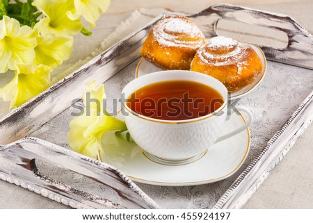 Sweet cinnamon bun rolls and cup of tea on vintage serving tray Stock photo © TasiPas