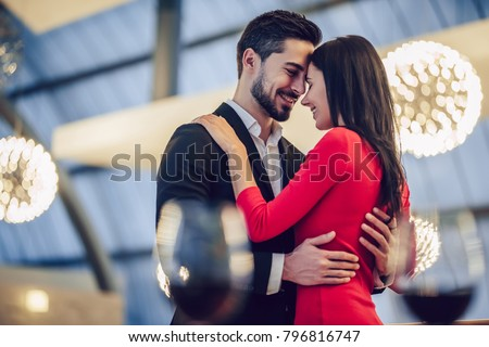 Handsome man with glass of wine with smiling girl in lingerine Stock photo © konradbak