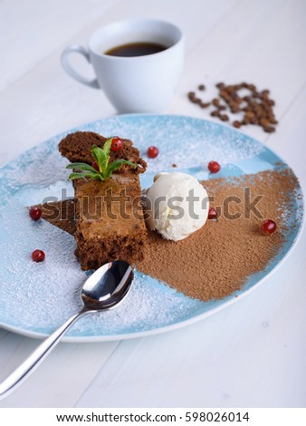 Chocolate brownie with ice cream on a blue plate next to a cup o Stock photo © d_duda