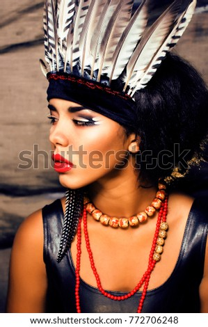 young pretty woman with make up like red indian, futher in hair, Stock photo © iordani