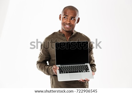 Stock photo: Smiling pensive african man showing blank laptop computer screen