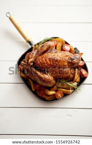 Grilled whole chicken in cast iron black pan with potatoes, tomatos and rosemary Stock photo © dash