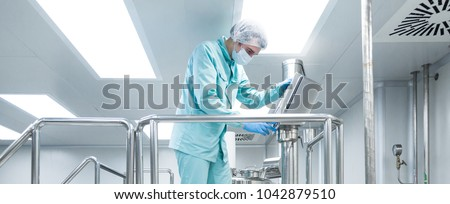 Сток-фото: Pharmaceutical Factory Man Worker In Protective Clothing Working On Equipment In Sterile Working Con