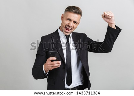 Image of cheerful man 30s in formal suit clenching fists while t Stock photo © deandrobot