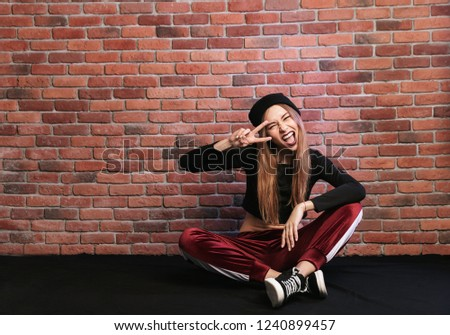 Photo of teenage hip hop dancer or sporty woman, sitting on floo Stock photo © deandrobot