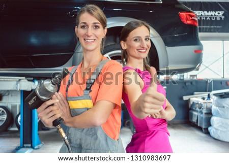 Portrait of a beautiful female auto mechanic next to her happy customer Stock photo © Kzenon