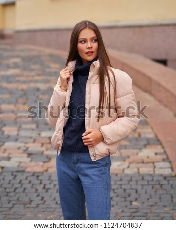 Young pretty woman dressed in blue jeans and pink jacket with fresh roses in a back pocket and her h Stock photo © artjazz