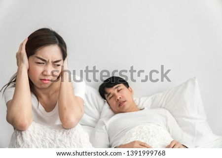 young woman lying on a bed covered her ears because of the noise in the window after the bed you ca stock photo © galitskaya