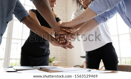 Team people stacking hands together over table engaged in teambu Stock photo © boggy
