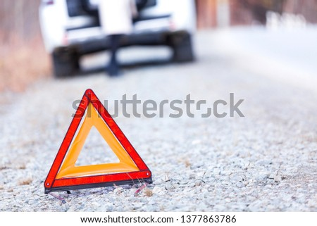 Closeup shot of warning red triangle sign, broken car and girl  Stock photo © Nobilior