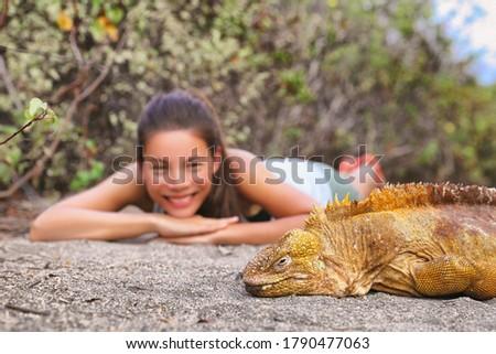 Galapagos islands tourist woman at yellow land iguana on Urbina Bay sand beach panoramic banner. Asi Stock photo © Maridav