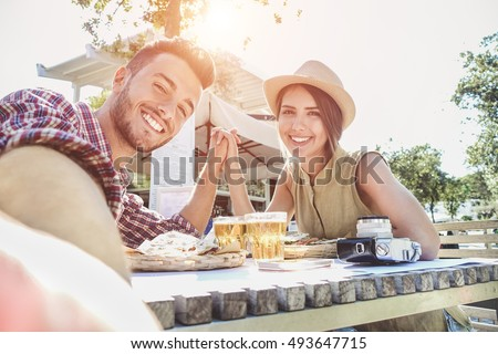 Happy selfie couple tourists on USA travel taking photo at sunset on Florida beach. Smiling Asian wo Stock photo © Maridav