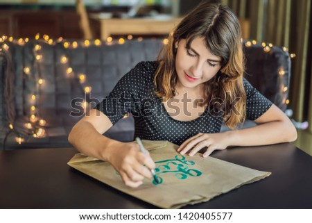Stock photo: Go green. Calligrapher Young Woman writes phrase on white paper. Inscribing ornamental decorated let