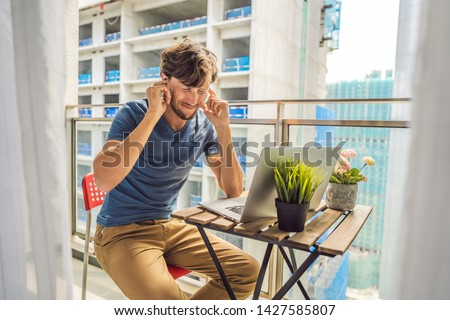 Young man trying to work on the balcony annoyed by the building works outside. Noise concept. Air po Stock photo © galitskaya