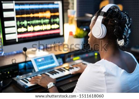 Jóvenes músico auriculares mirando sonido pantalla del ordenador Foto stock © pressmaster