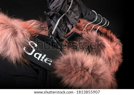 Sale sign. A lot of black coats, jacket with fur on hood hanging on clothes rack. Black background.  Stock photo © Illia