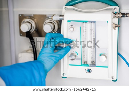 Gloved hand of paramedic regulating level of something on medical equipment Stock photo © pressmaster