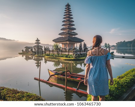 Young woman traveler in the background of Pura Ulun Danu Bratan, Bali. Hindu temple surrounded by fl Stock photo © galitskaya