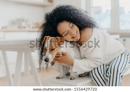 Smiling woman embraces pet with love, has happy mood, pose together near beautiful decorated Christm Stock photo © vkstudio