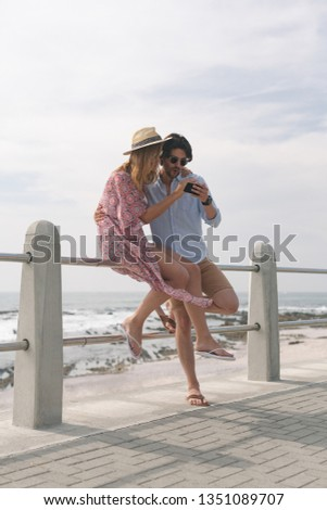 Side view of young Caucasian couple reviving photos while sitting at railing on beach on a sunny day Stock photo © wavebreak_media