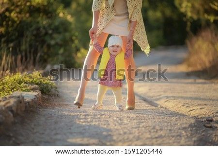 Mom performs the duties of a parent and helps her daughter to take the first steps Stock photo © ElenaBatkova