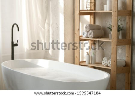 Large porcelain white bathtub and wooden shelves against grey wall in bathroom Stock photo © pressmaster