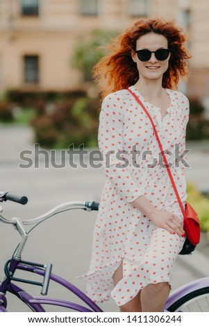 Photo of glad red haired woman with gentle smile, spends leisure time riding bicycle on city streets Stock photo © vkstudio