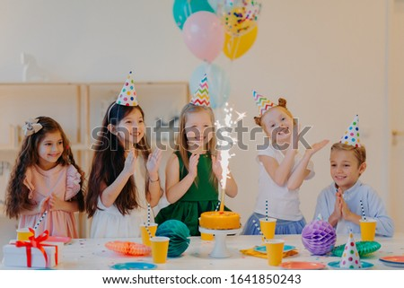 Children and holiday concept. Glad five friends look gladfully on cake with sparkle, celebrate birth Stock photo © vkstudio