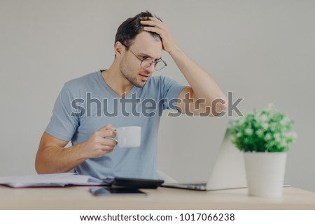 Сток-фото: Young Frustrated Male Does Paperwork Reads With Puzzled Expression Unpleasant Information On Laptop