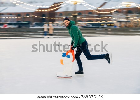 Young male begginer learns skating with help of special figure, leans at it, being on ice rink cover Stock photo © vkstudio