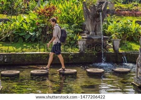 Young man tourist in Taman Tirtagangga, Water palace, Water park, Bali Indonesia BANNER, LONG FORMAT Stock photo © galitskaya
