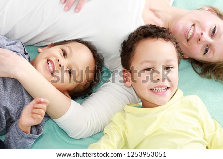 Photo of adorable small child and her mother have fun together in bed, tickle each other, smile joyf Stock photo © vkstudio