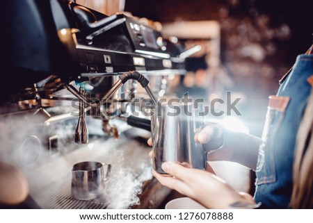 Barista whipped milk in the coffee machine in the foam for the preparation of the drink. Slow motion Stock photo © artjazz