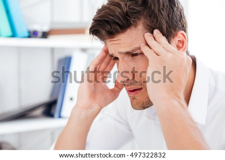 closeup of a young angry business man having a stress headache stock photo © hasloo
