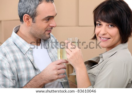 couple drinking champagne in front of a pile of cardboard boxes stock photo © photography33