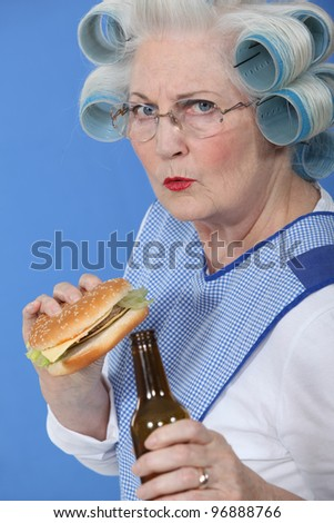senior with curlers in her hair drinking beer and eating hamburger Stock photo © photography33