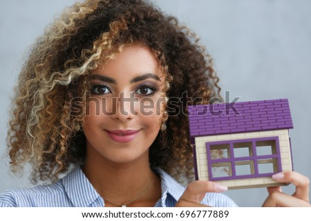 Smiling businesswoman holding a miniature house with the camera focus on the objecty Stock photo © wavebreak_media