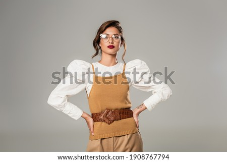 woman in leather clothes standing with hands on hips and looking Stock photo © feedough