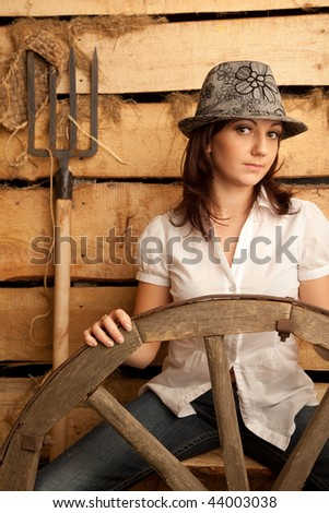 Portrait of girl in hat in hayloft with pitchfork and bast shoes. Vertical format. Stock photo © Paha_L