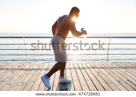 Serious african young sportsman running and holding water bottle outdoors Stock photo © deandrobot
